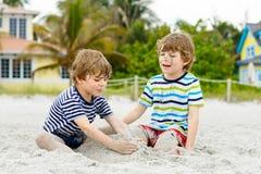 Deux garçons de petits enfants ayant l'amusement sur la plage tropicale Photos libres de droits