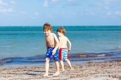 Deux garçons de petits enfants ayant l'amusement sur la plage tropicale Photographie stock libre de droits