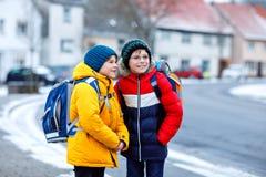 Deux garçons de petits enfants de classe élémentaire marchant à l'école pendant les chutes de neige Enfants heureux ayant l'amuse images stock