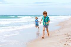 Deux garçons de petits enfants courant sur la plage de l'océan Images libres de droits