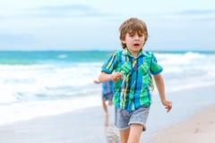 Deux garçons de petits enfants courant sur la plage de l'océan Image libre de droits