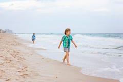 Deux garçons de petits enfants courant sur la plage de l'océan Photographie stock