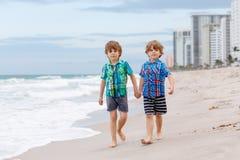Deux garçons de petits enfants courant sur la plage de l'océan Photo libre de droits