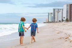 Deux garçons de petits enfants courant sur la plage de l'océan Photos libres de droits