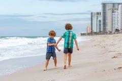 Deux garçons de petits enfants courant sur la plage de l'océan Image stock