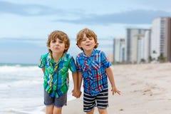 Deux garçons de petits enfants courant sur la plage de l'océan Photo stock
