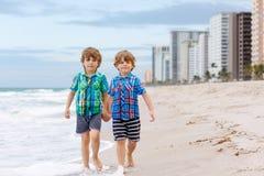 Deux garçons de petits enfants courant sur la plage de l'océan Photos stock
