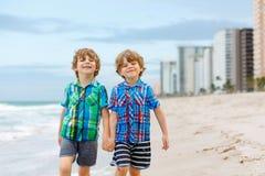 Deux garçons de petits enfants courant sur la plage de l'océan Photographie stock libre de droits
