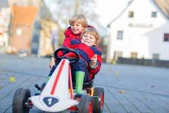Deux garçons de petits enfants jouant avec des voitures de jouet, dehors Images libres de droits