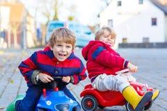 Deux garçons de petits enfants jouant avec des voitures de jouet, dehors Photographie stock libre de droits