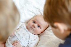Deux garçons de petits enfants jouant avec la fille nouveau-née de soeur de bébé image stock