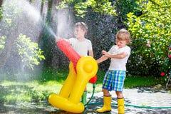 Deux garçons de petits enfants jouant avec une arroseuse de l'eau de tuyau d'arrosage Photographie stock