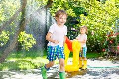 Deux garçons de petits enfants jouant avec une arroseuse de l'eau de tuyau d'arrosage Photos stock
