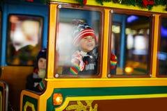 Deux garçons de petits enfants sur le carrousel au marché de Noël Image libre de droits