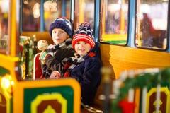 Deux garçons de petits enfants sur le carrousel au marché de Noël Photo stock