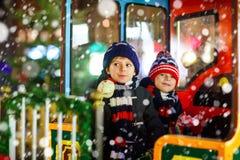 Deux garçons de petits enfants sur le carrousel au marché de Noël Photo libre de droits