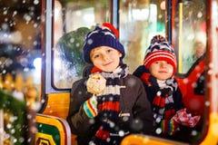 Deux garçons de petits enfants sur le carrousel au marché de Noël Photographie stock libre de droits