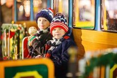 Deux garçons de petits enfants sur le carrousel au marché de Noël Photographie stock