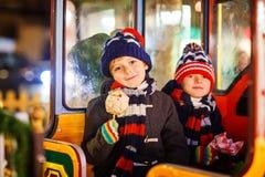 Deux garçons de petits enfants sur le carrousel au marché de Noël Photos stock