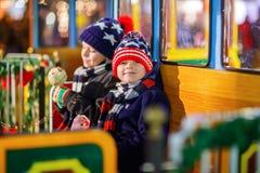 Deux garçons de petits enfants sur le carrousel au marché de Noël Images libres de droits
