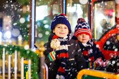 Deux garçons de petits enfants sur le carrousel au marché de Noël Photos libres de droits