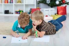 Deux garçons dessinent Santa Claus sur le papier sur le plancher dans la crèche Boîtes avec des cadeaux sous l'arbre image stock