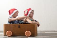 Deux garçons drôles dans un chapeau de Santa Claus jouent avec des chevaux dessinés sur le carton Les types ont l'amusement à la  Photos libres de droits