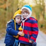 Deux garçons drôles d'enfant de mêmes parents de petit enfant étreignant le jour froid Images stock
