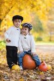 Deux garçons en parc, se reposant sur un grand potiron, souriant Image stock