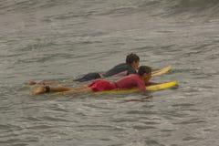Deux garçons entrent dans la mer pour surfer photographie stock libre de droits