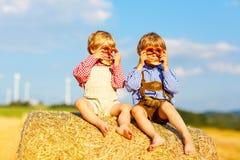 Deux garçons et amis de petit enfant s'asseyant sur la pile de foin Photographie stock