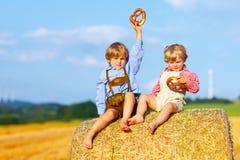 Deux garçons et amis de petit enfant s'asseyant sur la pile de foin Photos stock