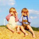 Deux garçons et amis de petit enfant s'asseyant sur la pile de foin Photo libre de droits