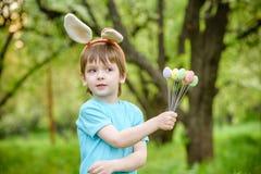 Deux garçons et amis de petits enfants dans des oreilles de lapin de Pâques pendant l'oeuf traditionnel chassent au printemps le  Photo stock