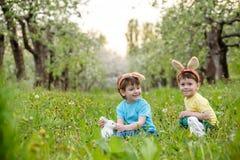 Deux garçons et amis de petits enfants dans des oreilles de lapin de Pâques pendant l'oeuf traditionnel chassent au printemps le  Photos libres de droits
