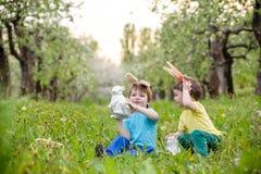 Deux garçons et amis de petits enfants dans des oreilles de lapin de Pâques pendant l'oeuf traditionnel chassent au printemps le  Images stock