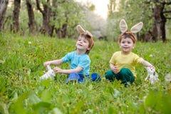 Deux garçons et amis de petits enfants dans des oreilles de lapin de Pâques pendant l'oeuf traditionnel chassent au printemps le  Images libres de droits