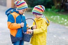 Deux garçons et amis de petits enfants faisant l'oeuf de pâques traditionnel chasser Photographie stock