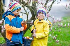 Deux garçons et amis de petits enfants faisant l'oeuf de pâques traditionnel chasser Photo stock