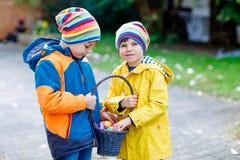 Deux garçons et amis de petits enfants faisant l'oeuf de pâques traditionnel chasser Images libres de droits