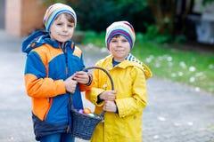 Deux garçons et amis de petits enfants faisant l'oeuf de pâques traditionnel chasser Photos libres de droits