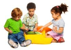 Deux garçons et fille jouant avec le comprimé Photographie stock libre de droits