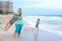 Deux garçons et mère de petits enfants sur la plage de l'océan Image stock