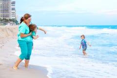 Deux garçons et mère de petits enfants sur la plage de l'océan Photos stock