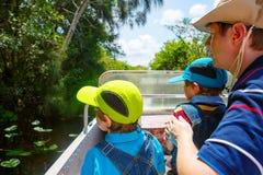 Deux garçons et père de petits enfants faisant air le bateau voyager dans les marais se garent Photographie stock