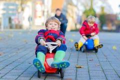 Deux garçons et père de petits enfants jouant avec des voitures, dehors Photos stock