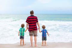 Deux garçons et père de petits enfants sur la plage de l'océan Images stock
