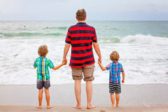 Deux garçons et père de petits enfants sur la plage de l'océan Photos libres de droits
