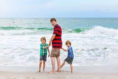 Deux garçons et père de petits enfants sur la plage de l'océan Photos stock