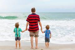 Deux garçons et père de petits enfants sur la plage de l'océan Image stock